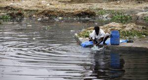 Mann wäscht Kleidung in verschmutztem Gewässer; Foto: Pijush Saha. Shiykh Seraj (flickr)