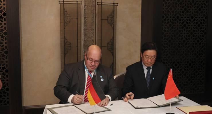 Bundesumweltminister Peter Altmaier und der stellvertretende Vorsitzende der chinesischen Energiebehörde Liu Qi unterzeichnen am 14. Januar 2013 am Rande der 3. IRENA-Versammlung in Abu Dhabi (Vereinigte Arabische Emirate) eine bilaterale Absprache zur zukünftigen Zusammenarbeit zum Ausbau der erneuerbaren Energien zwischen dem Bundesumweltministerium und der chinesischen Nationalen Energiebehörde (NEA)