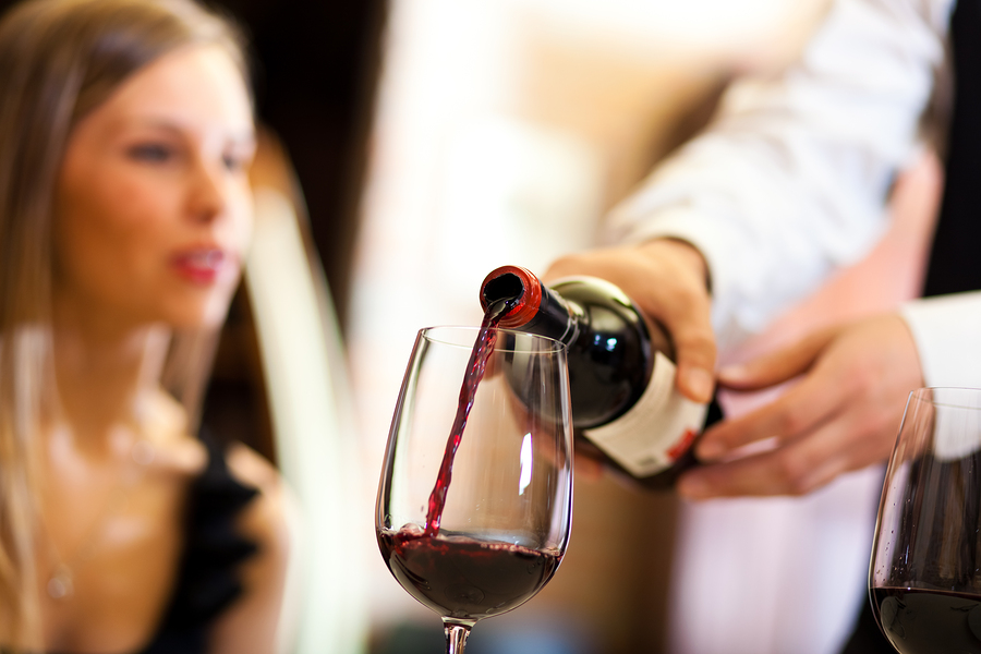 bigstock-Waiter-pouring-red-wine-to-a-w-45754489