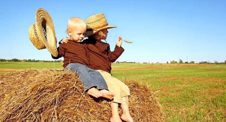 Kinder auf einem Strohballen