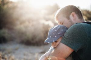 Mann mit Baby auf dem Arm, im Hintergrund Sonne und Büsche