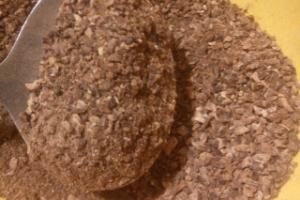 Bräunliches Pulver auf einem Löffel und in einer Schüssel
